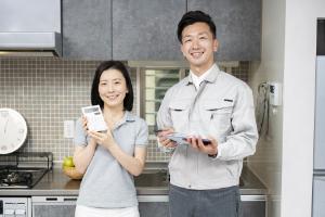 電卓を持った女性と作業着の男性の写真